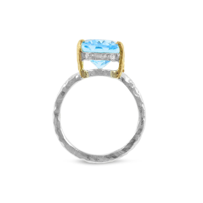 Ring handcrafted in sterling silver with 18ct yellow gold claws set with blue topaz