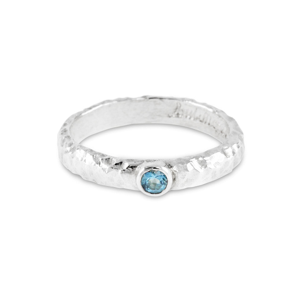 Handmade blue topaz ring in silver with an organic texture.