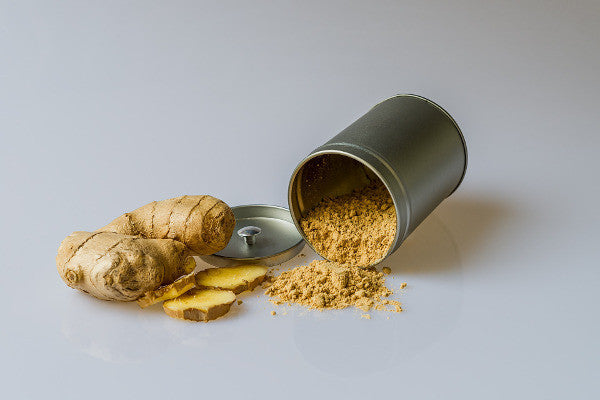image of a ginger root next to a silver container full of ginger powder
