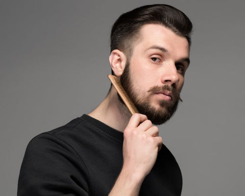 A man combing his beard with a sharp tooth comb