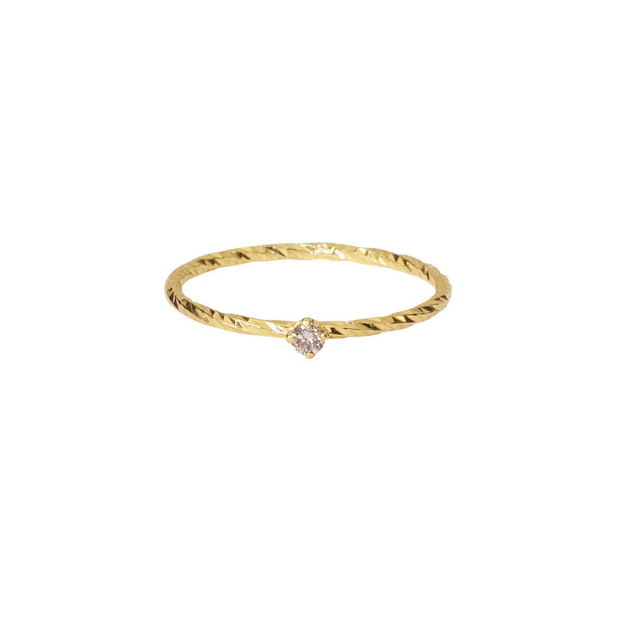 A sparkling band stacking ring in gold with a claw set champagne diamond.