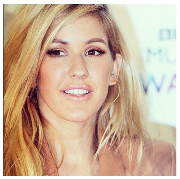Ellie Goulding wearing the Supernova Octagonal Hoop earrings in gold.