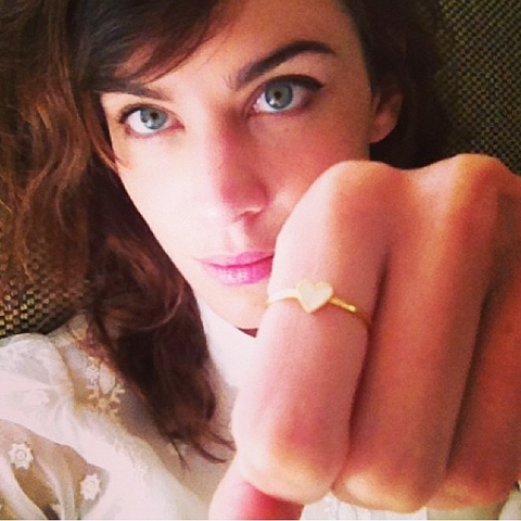 Alexa Chung wearing the White Enamel Heart ring in gold.