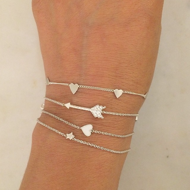 Selection of silver bracelets worn by customer.