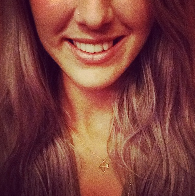 The Bow and Arrow Necklace in gold worn by customer.