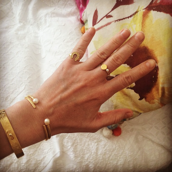 Selection of rings and bracelets in gold worn by customer.