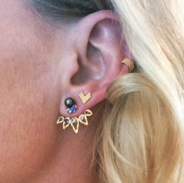 Selection of Cosmic and Braveheart earrings in gold, worn by customer.