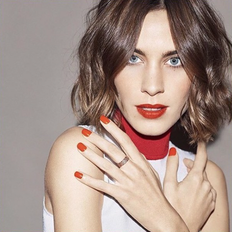 Alexa Chung wearing the Equine Wide Band ring in gold.