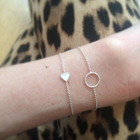 White Enamel Heart bracelet and Protective Circle bracelet in silver worn by customer.