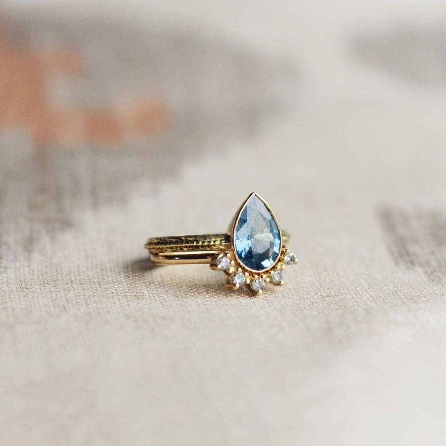 The pear shaped Harmony engagement ring with a blue grey sapphire, combined with a tiara wedding band with salt & pepper diamonds.
