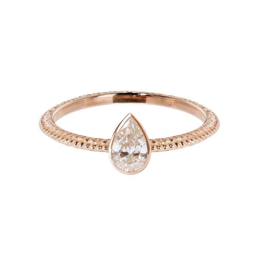 The Harmony engagement ring with a pear shaped white diamond which is bezel set. The textured band has a beautiful beaded line running down the centre. Made from 18 carat rose gold.