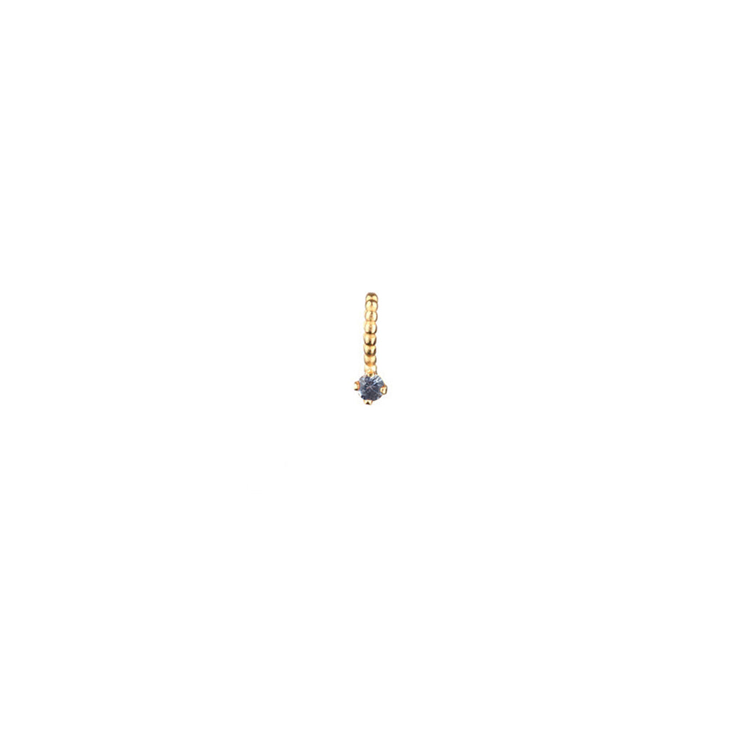 Light blue sapphire charm with beaded bail in gold.