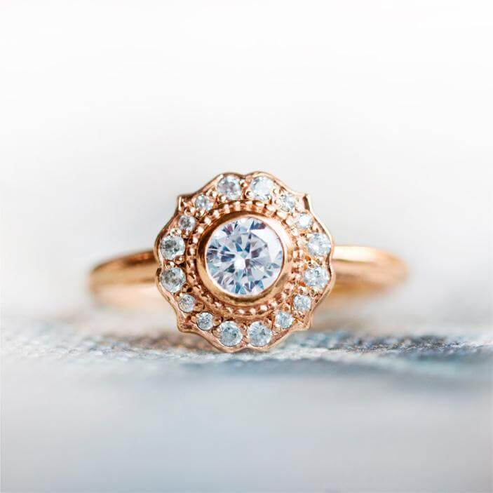 The Paradise white diamond halo engagement ring has a traditional vintage feel with a modern edge. Made from 18 carat rose gold.