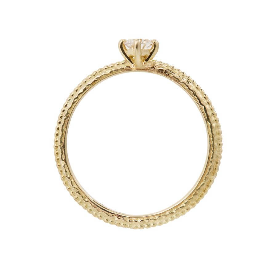 Side view of the white diamond solitaire Tender Love engagement ring in 18 carat yellow gold, featuring a delicate beaded band.
