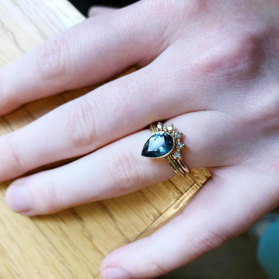 Wearing the pear shaped Harmony engagement ring with a blue grey sapphire, combined with the Titania tiara wedding band with salt & pepper diamonds.