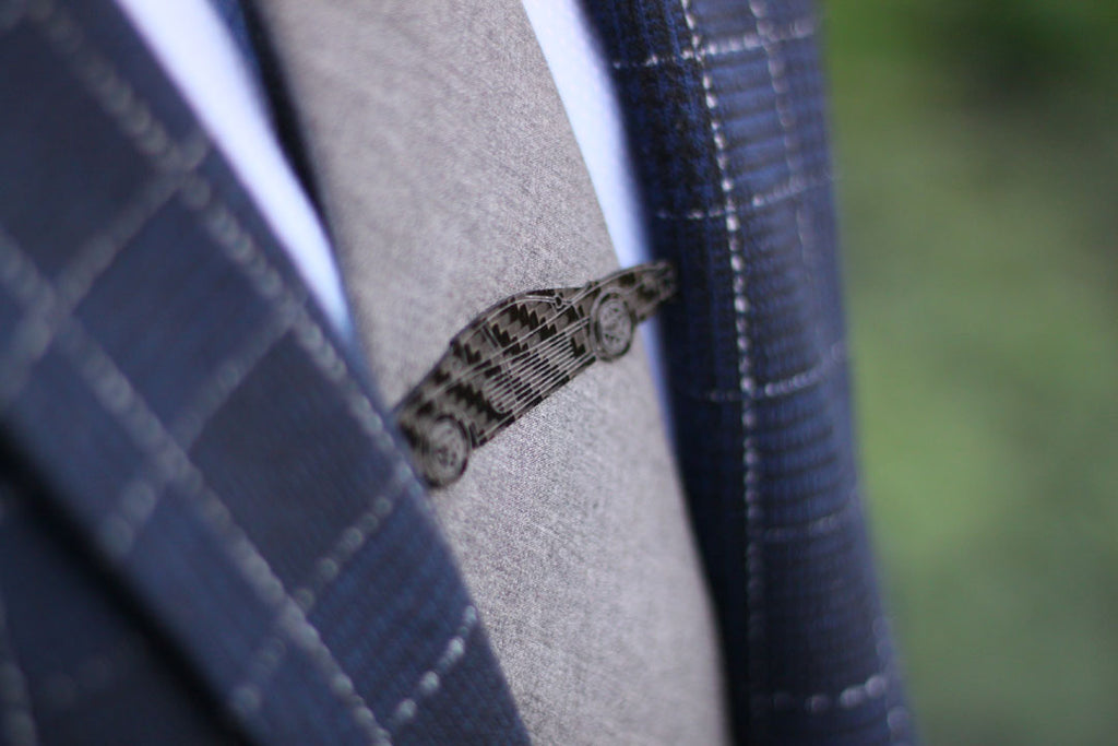 Close up of a STEVS carbon fiber tie clip on a man's tie. Made in Canada