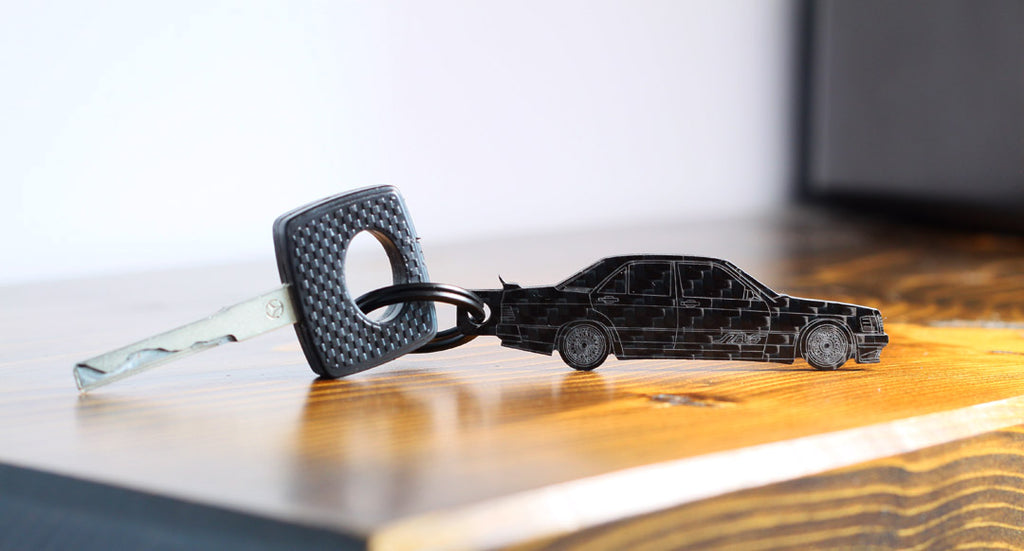 Close up of a custom STEVS carbon fiber keychain. This keychain is made to look like a Mercedes Benz 190E.  Designed and made in Canada.
