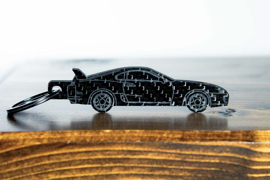 An MK4 Supra carbon fiber keychain, front view