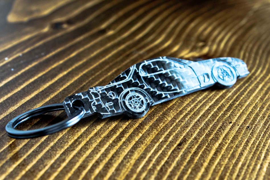 An FD RX-7 carbon fiber keychain, angle view