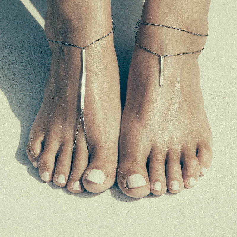 Foot bracelet handmade in brass and silver shown on model.
