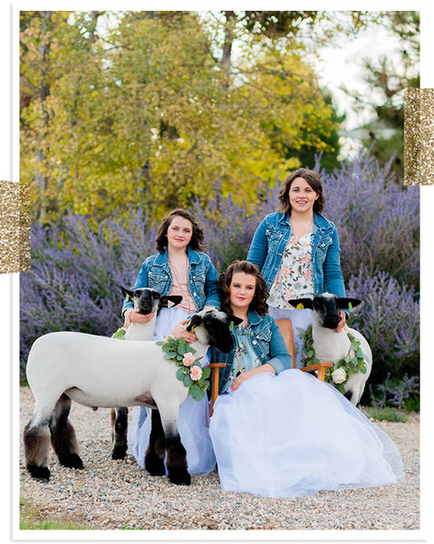 Girls with their sheep in white dreses with floral wreaths