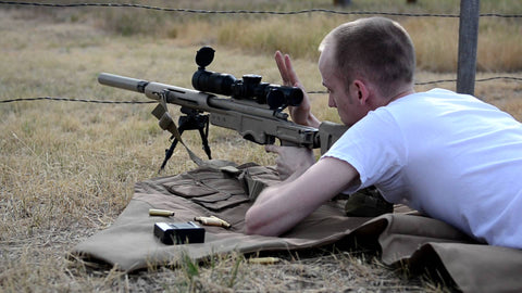 shooting prone with a silencer on a rifle