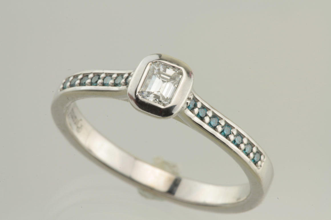 Emerald cut diamond white gold ring with blue diamonds