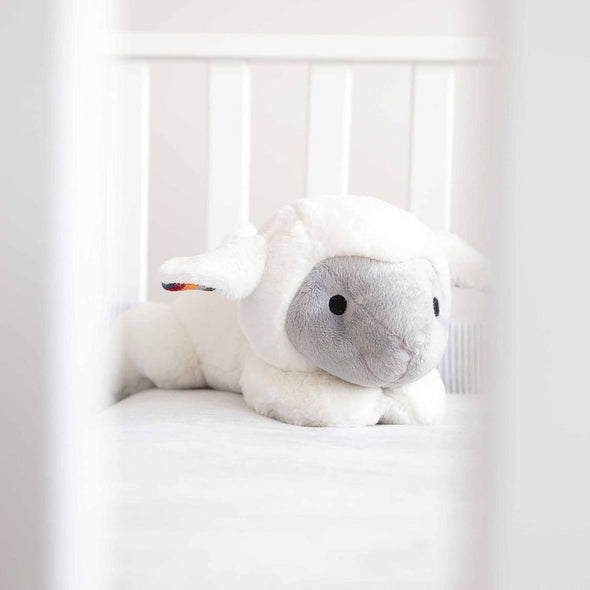 Liz the Lamb Soft Toy Comforter sitting in baby's cot