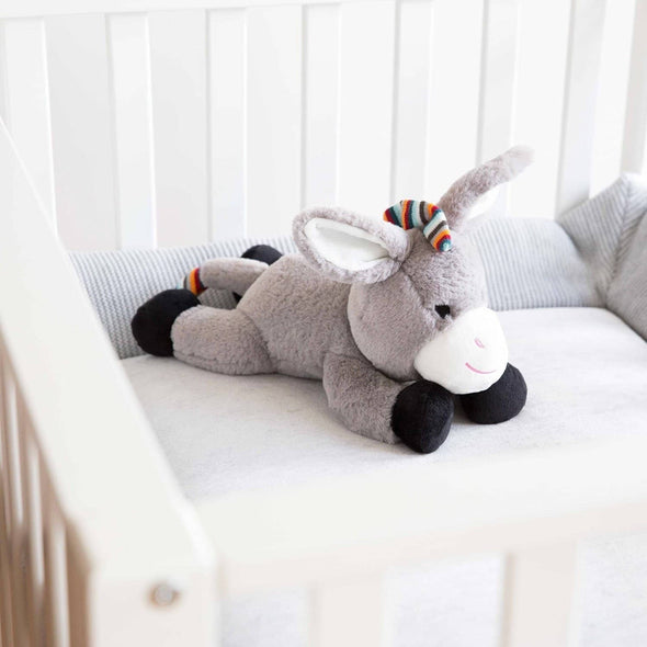Don the Donkey laying in baby's cot