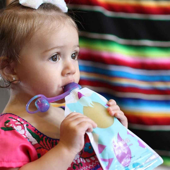 Toddler eating out of reusable food pouch