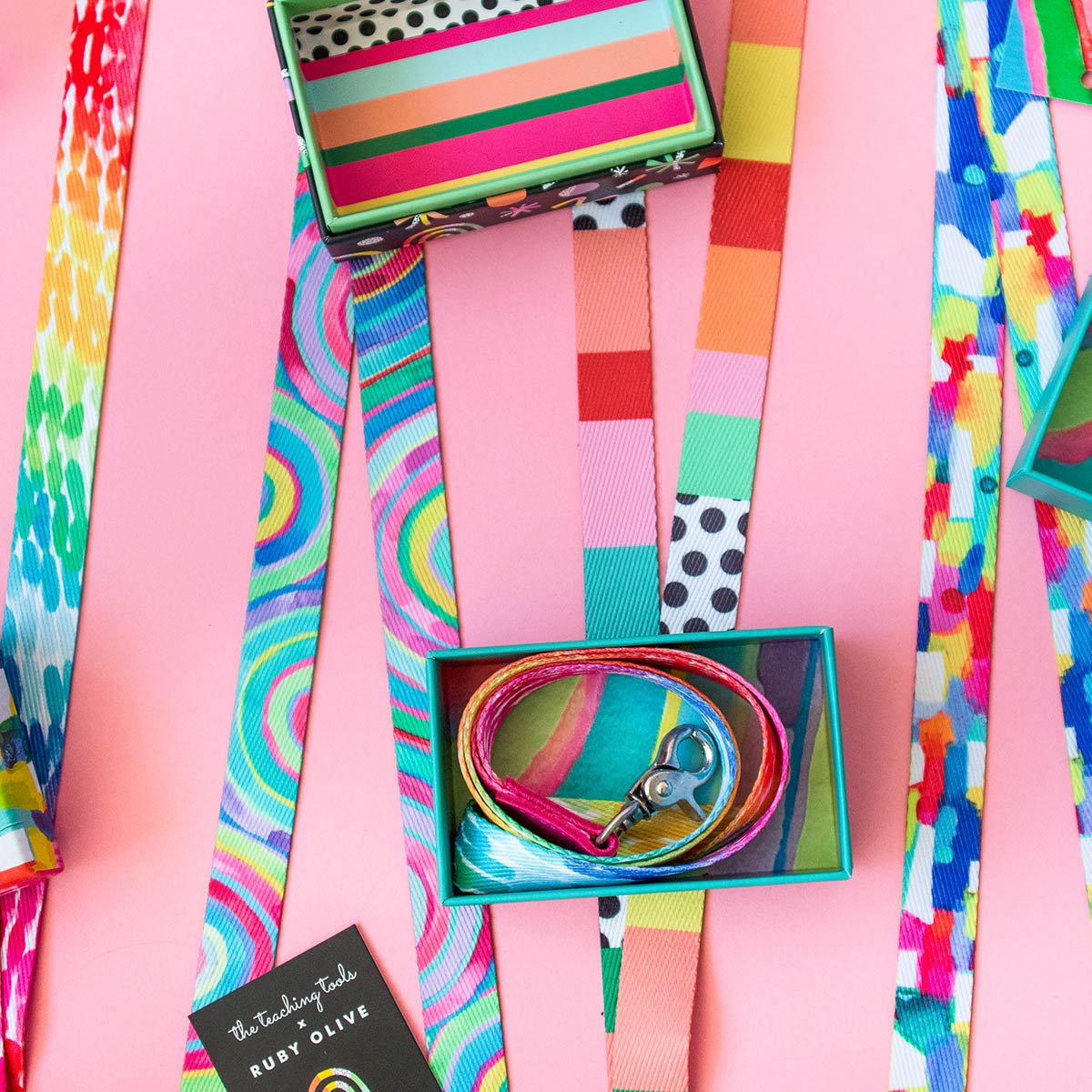 Colourful Ruby Olive lanyards laying on pink background