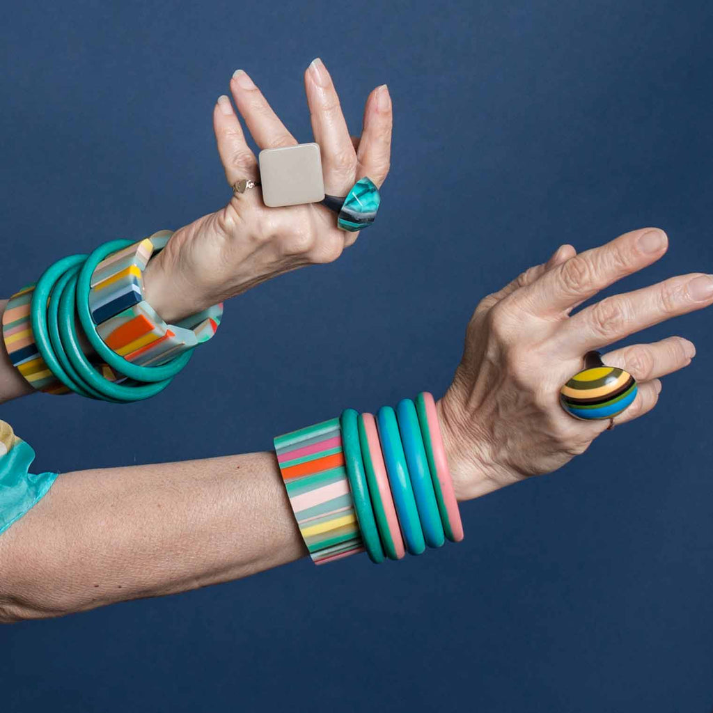 Hands with Ruby Olive colourful bangles and bold rings on navy blue background