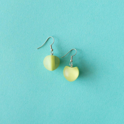 Ruby Olive Jewellery green seed pod drop earrings on blue background