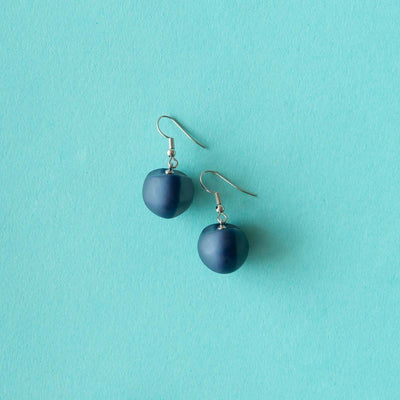 Ruby Olive Jewellery navy seed pod drop earrings on blue background