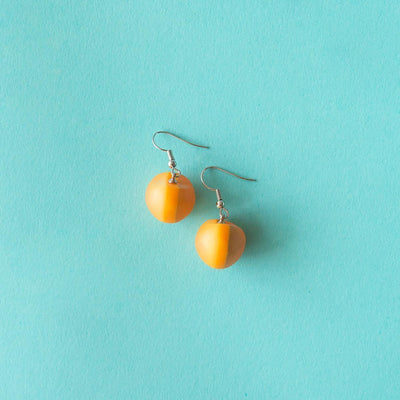 Ruby Olive Jewellery yellow seed pod drop earrings on blue background