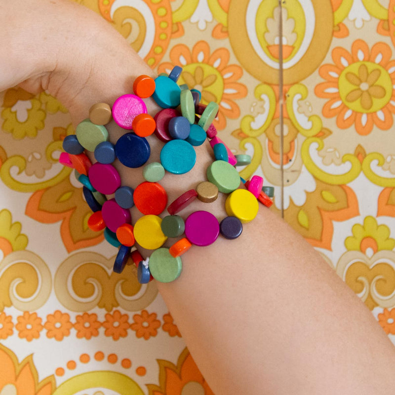 Five bright and colourful bracelets on a yellow background.