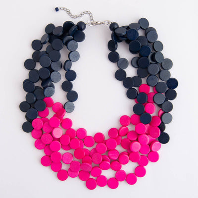 Bright pink and navy stacked wood beaded necklace on a white background.