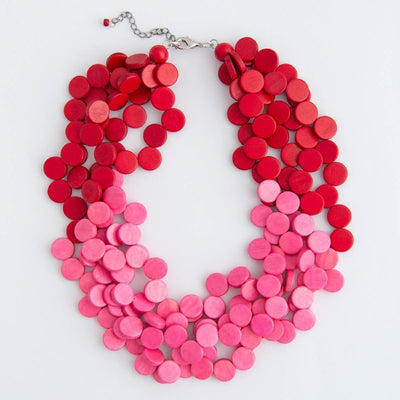 Bright pink and red stacked wood beaded necklace on a white background.