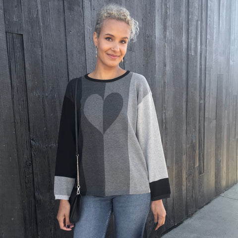 This cozy pullover features a flattering vertical stripe in a heather grey gradient, with a subtle 2-toned heart motif. Additional contrast stripes and cuffs on both sleeves.    Soft and lightweight fine gauge 100% cotton pullover with a jewel neckline and long sleeves.  Rib trims.  Mid hip length. Roomy fit.  Machine wash cold, lay flat to dry.   OK to dry clean.   Made in USA from imported yarn.
