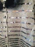 Gunmetal sequins with a bit of iridescence adorn this fine gauge grey heather cardigan in Ramie/Cotton.  Detachable fake fur collar and pretty faceted buttons in black.  Long sleeves. Slight shape to the waist.  Length is high hip. Vintage 90s glam sequin cardigan
