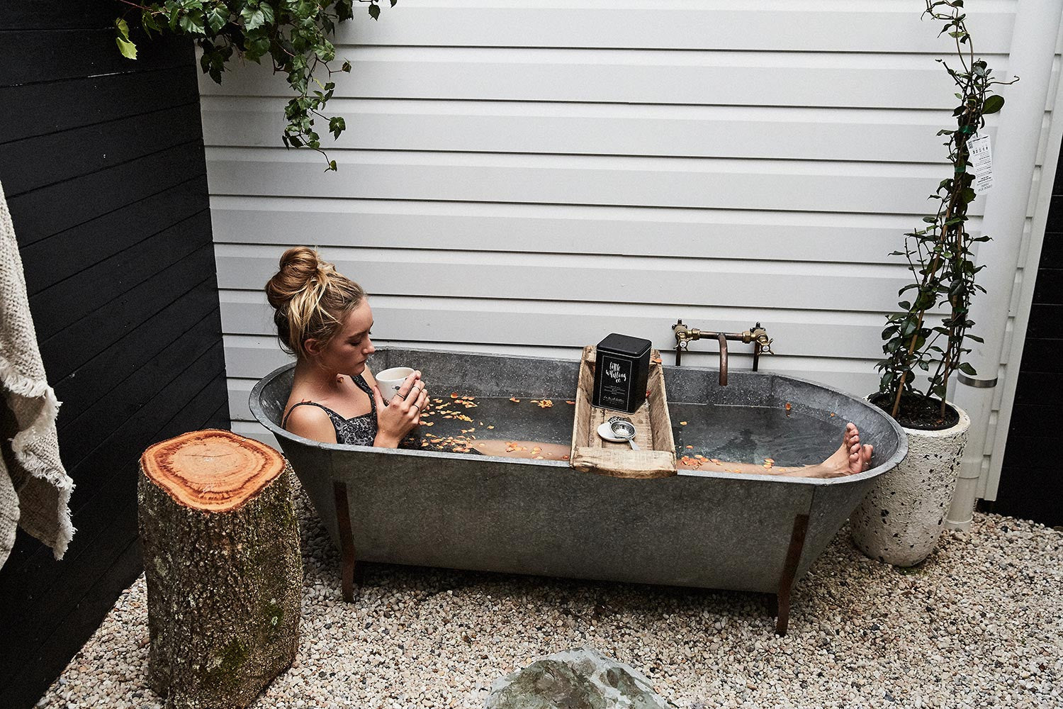 Woman in modern outside tub drinking tea
