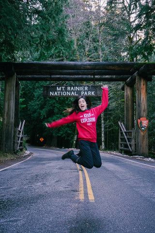 girl jumping in keep exploring sweater in front of mount rainier