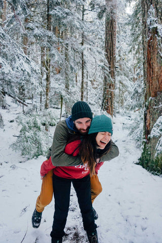 Guy riding piggyback on fiance in snowy forest