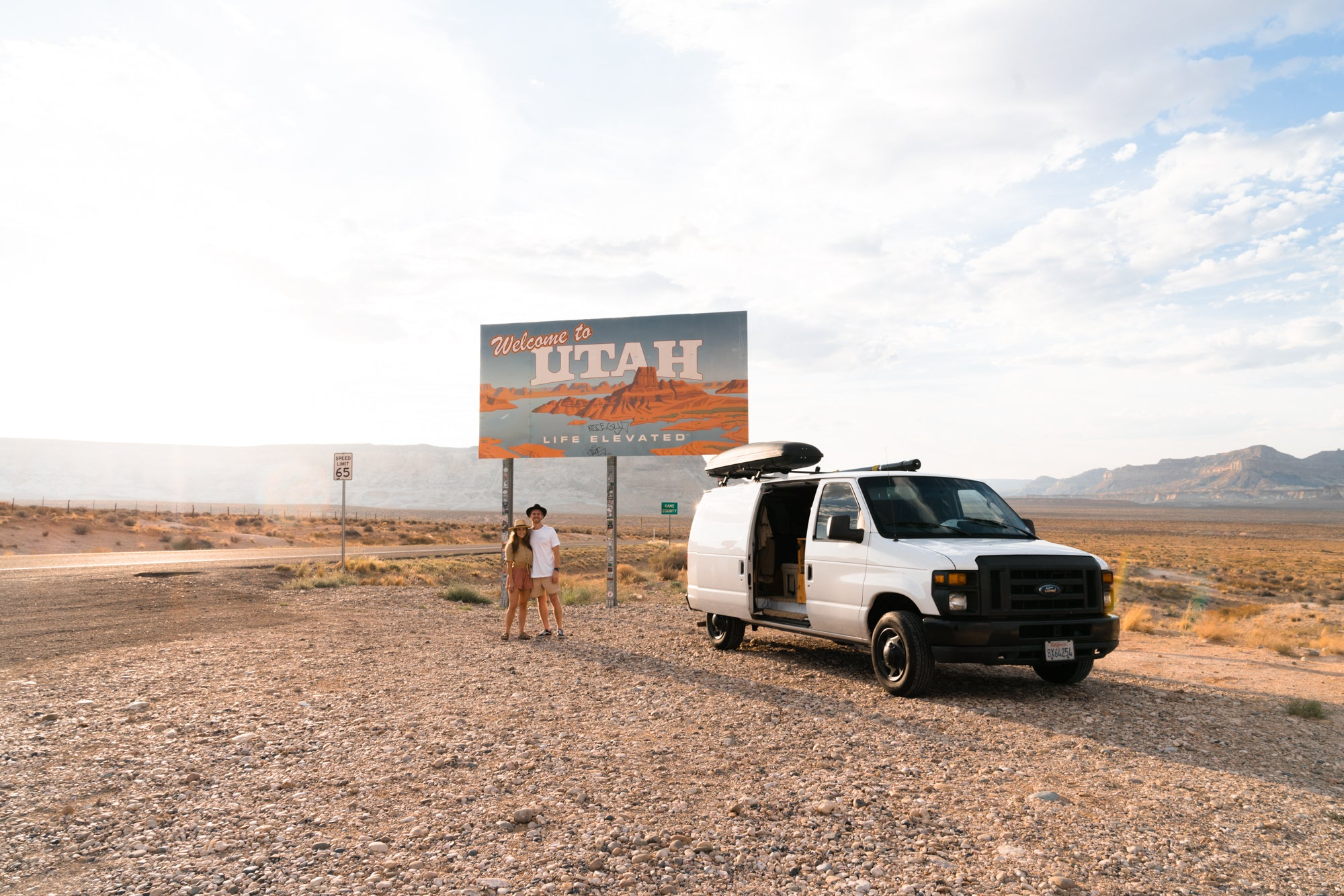 "Van in front of ""Welcome to Utah"" sign"