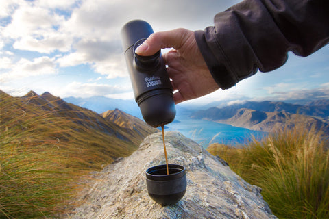 mini handheld espresso maker pouring coffee in the mountains by a lake