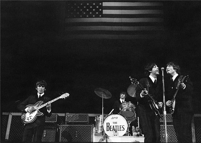 The Beatles onstage with flag, 1964 by Curt Gunther