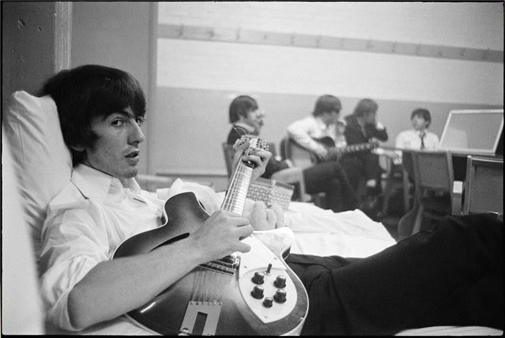 George Harrison on the bed with guitar, 1964 by Curt Gunther