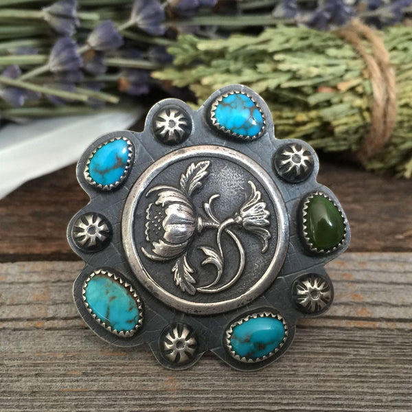 The Optimist Bouquet Ring is handcrafted from sterling silver and natural Nevada turquoise.  It was handmade by Nikki Leigh of Osa Metal Studio.