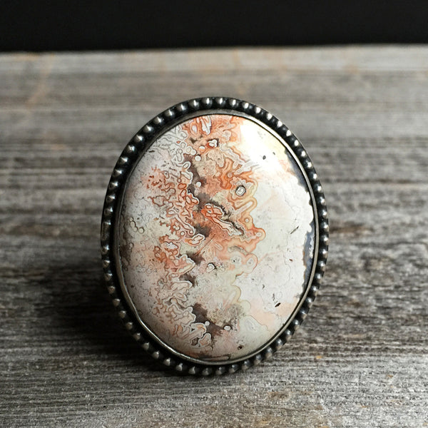 The Lucid Dream Ring features an orange and white crazy lace agate stone set in sterling silver.  It was handmade by metalsmith Nikki Leigh of Osa Metal Studio.