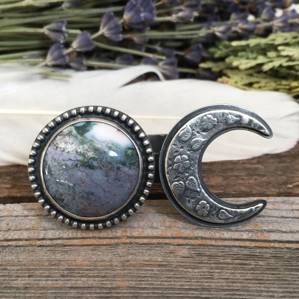 The Alien Meadow Ring is handcrafted from purple agate and sterling silver.  It features a floral moon and planet theme, and is handmade by Nikki Leigh of Osa Metal Studio.